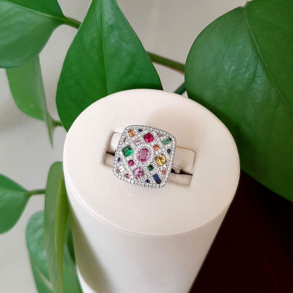 14k white gold ring with diamonds, sapphires and garnets in different colors.