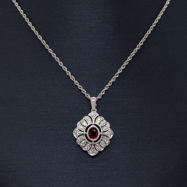 14K white gold diamond necklace with filigree detail and oval ruby in center