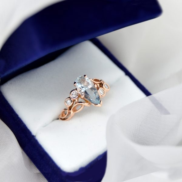 14K rose gold ring designed by Morgan's Treasure with bezel set diamonds in an organic open design with pear cut aquamarine gemstone