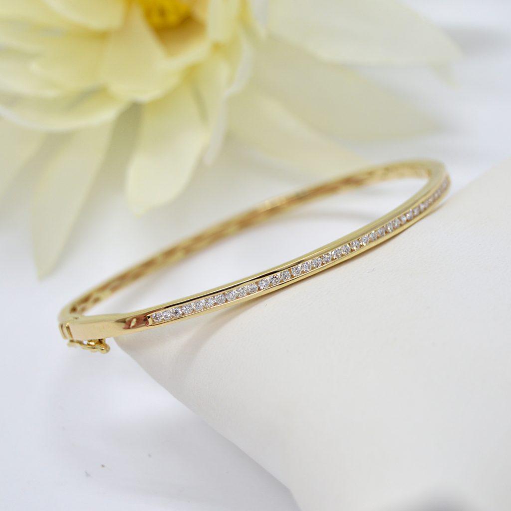 14K yellow gold bracelet with a single row of diamonds, hinged bangle by Allison Kaufman