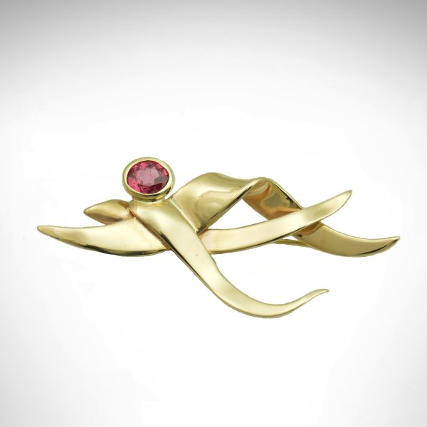 14k yellow gold brooch with dark pink oval sapphire in bezel, pin with wave-like design, custom design
