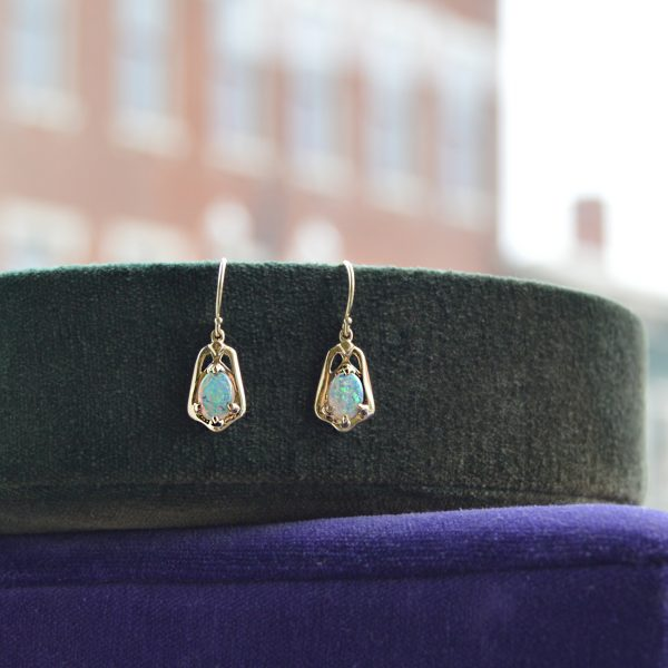 Oval 7 x 5mm translucent white opals set in vintage/ art nouveau inspired dangle earrings in 14K yellow gold. Designed by Morgan's Treasure
