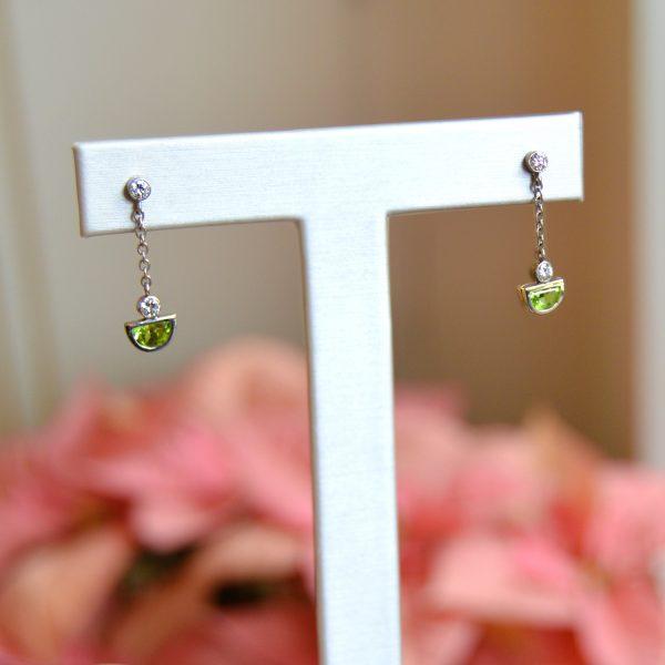 bezel-set peridot cut in half moon shape with diamonds and chain as dangle post earrings in 14K white gold