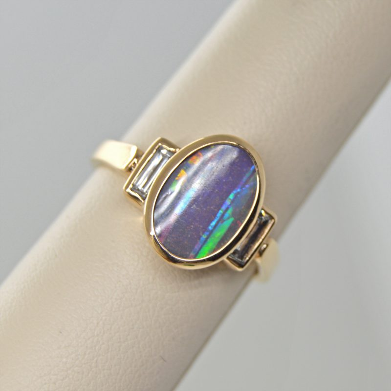 Australian Boulder Opal natural oval gemstone, bezel set oval three stone ring with baguette diamonds in 14k yellow gold ring. Designed by Morgan's Treasure in Westerville, OH