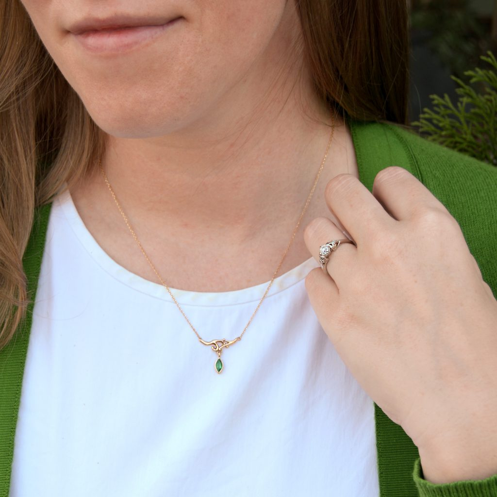 Model wearing custom necklace in 14k yellow gold with branch design and marquise cut natural emerald dangle