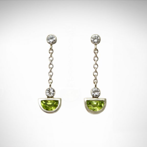 bezel-set peridot August birthstone cut in half moon shape with diamonds and chain as dangle post earrings in 14K white gold