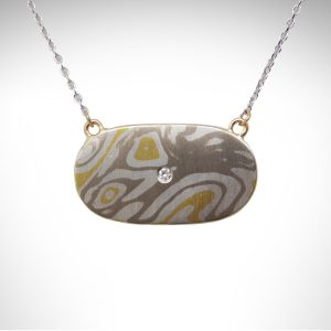 Mokume gane necklace in 18k yellow gold, 14k yellow gold, sterling silver and palladium white gold with a gypsy or flush set diamond in an oval shape, fastened to a white gold cable chain. horizontal necklace with organic lines in woodgrain inspired pattern of mixed metals, hand-fabricated into a minimalist necklace.