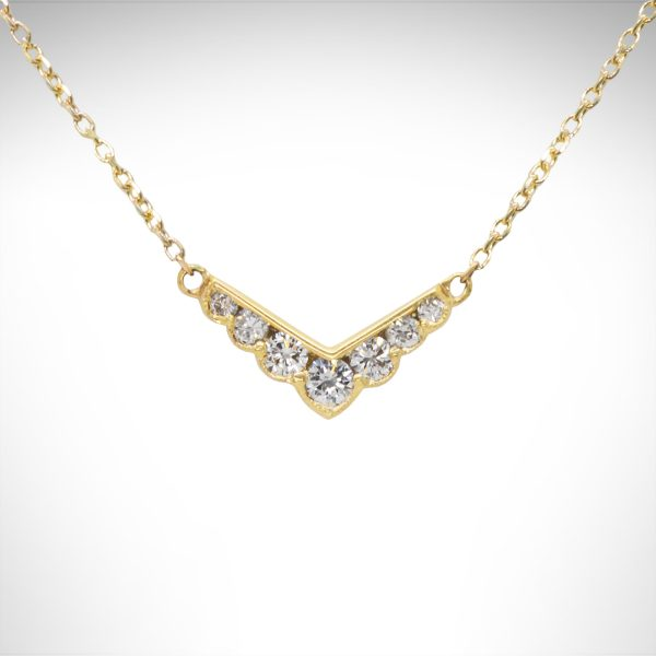 14k yellow gold bar necklace with v shape and diamonds with millgrain scalloped edge and cable chain.
