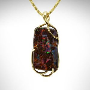 Boulder opal pendant in yellow gold with freeform openwork design, brown and multicolored elongated irregular rectangle shape on popcorn chain