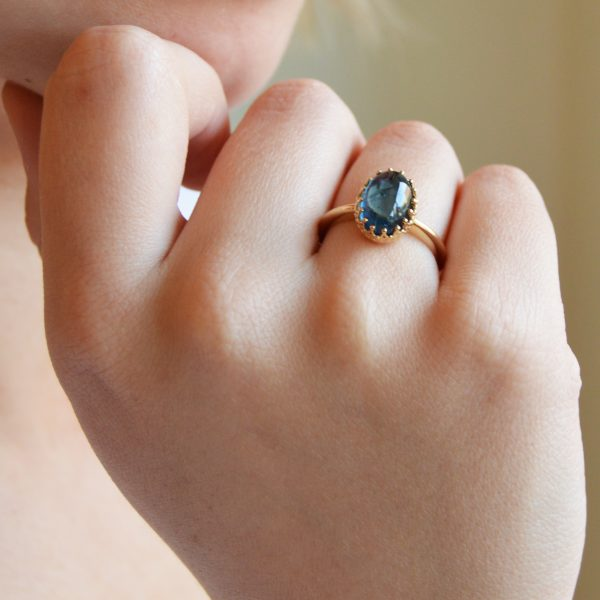 14ky gold ring with prong-set cabochon oval blue indicolite tourmaline gemstone.