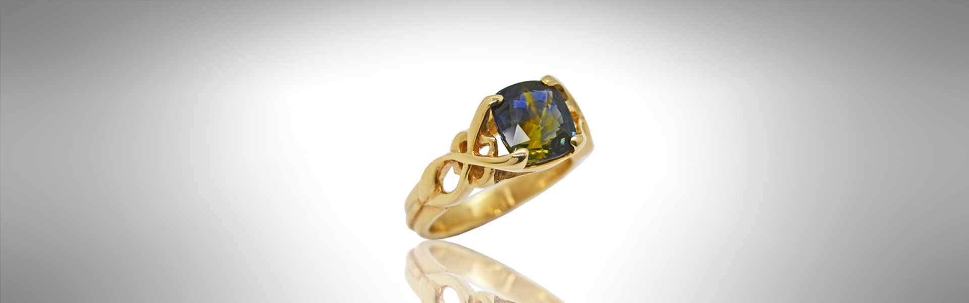 bicolor yellow and blue natural sapphire in 18kt yellow gold with diamonds in an intricate open ring design.