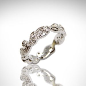 Carizza eternity band, a vine design with diamonds and millgrain in 18K white gold