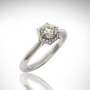 Hexagon halo engagement ring with round brilliant diamond, 6 prongs, white gold with true french pave-set diamonds.