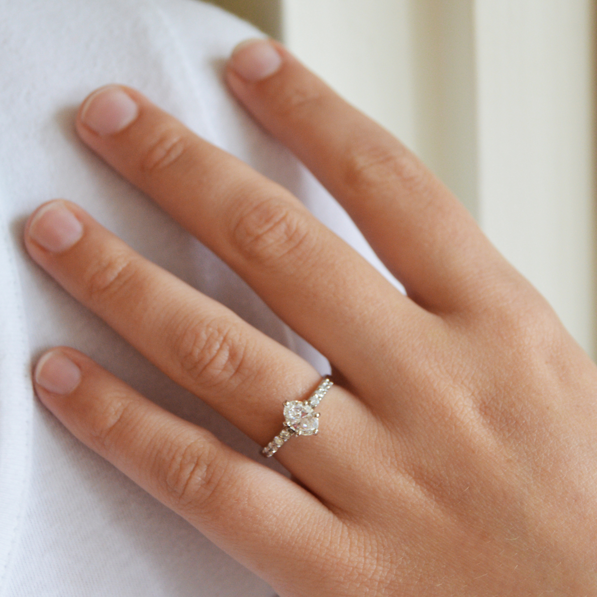 Oval engagement ring with shared prong shank diamonds and 6-prong oval diamond center stone.