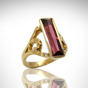 Pink tourmaline ring in yellow gold with scrolls and accent diamonds.