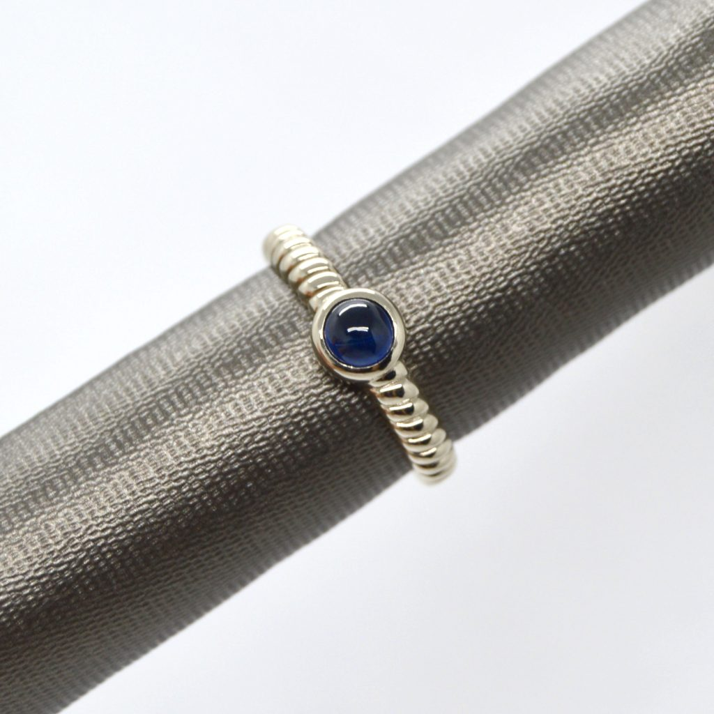 14K white gold ring with rope style shank and bezel set cabochon blue sapphire
