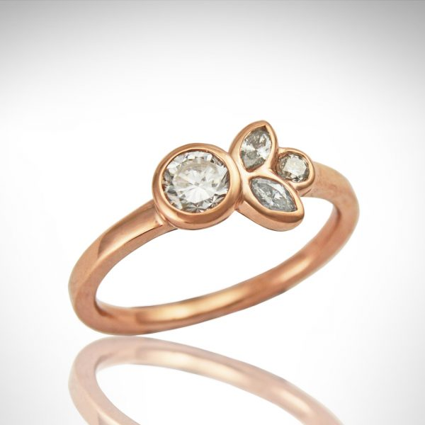 14k rose gold diamond ring with bezel-set round and marquise diamonds and simple band, minimalist design with floral/ leaf inspiration.