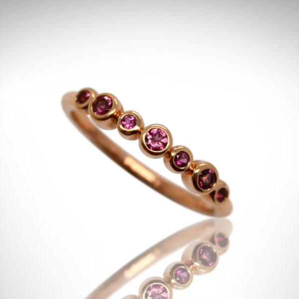 Pink tourmaline ring in alternating sizes of round bezel set stones in 14k rose gold, stackable ring