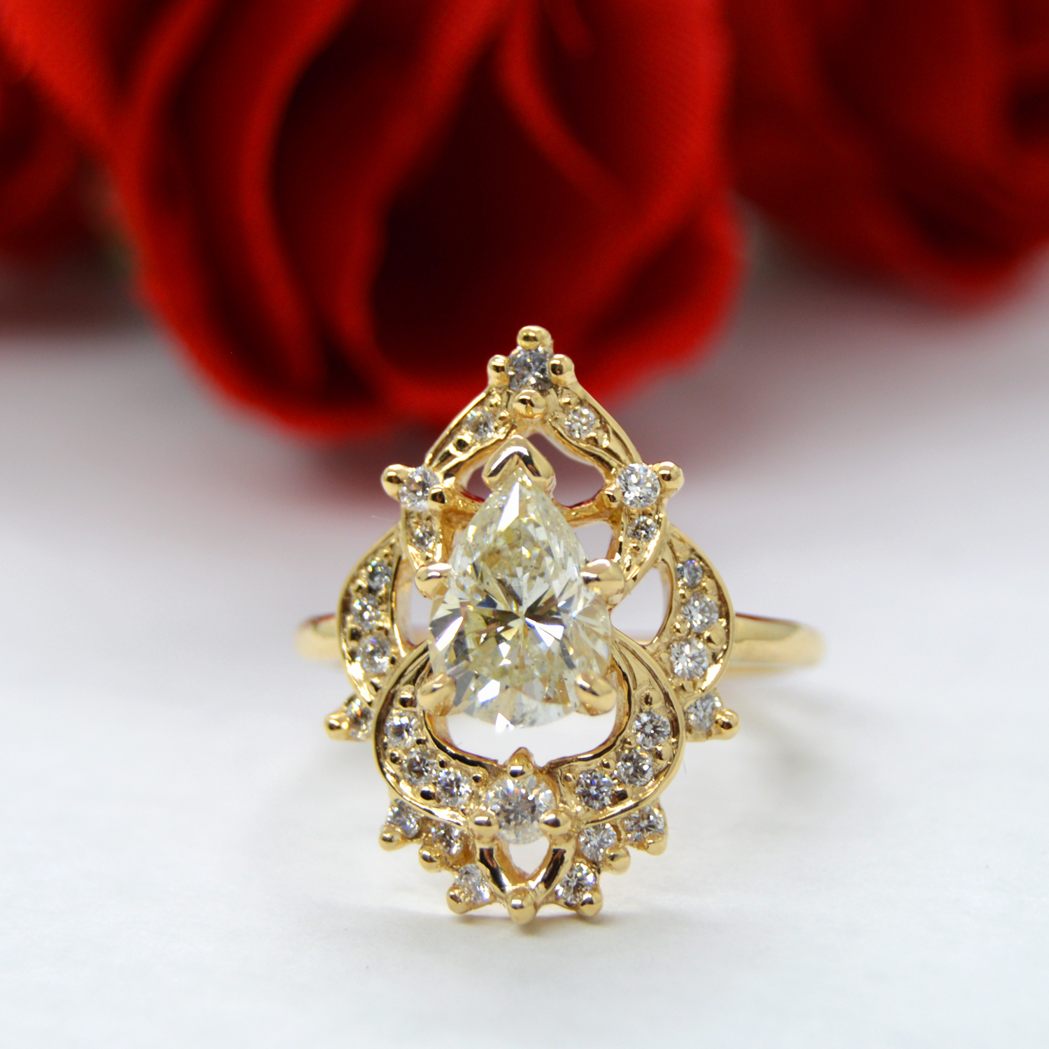 Custom engagement ring in 14K yellow gold with pear cut diamond, pave and prong set accents and open halo.
