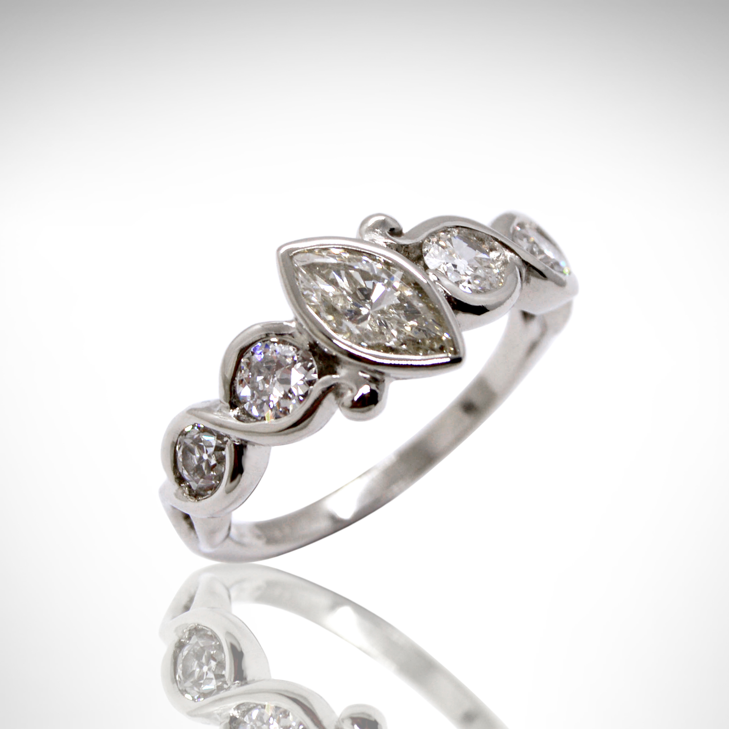 14K white gold ring with marquise center stone and round side stones in a twisted design with bezel setting