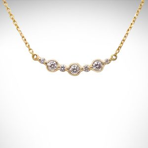diamond bar necklace with bezels, alternating sizes round diamonds in a horizontal bar connected to chain in 14Kt yellow gold