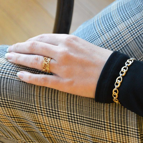 Model wearing 2 14KY stackable diamond rings and two tone diamond and gold link bracelet with brushed finish